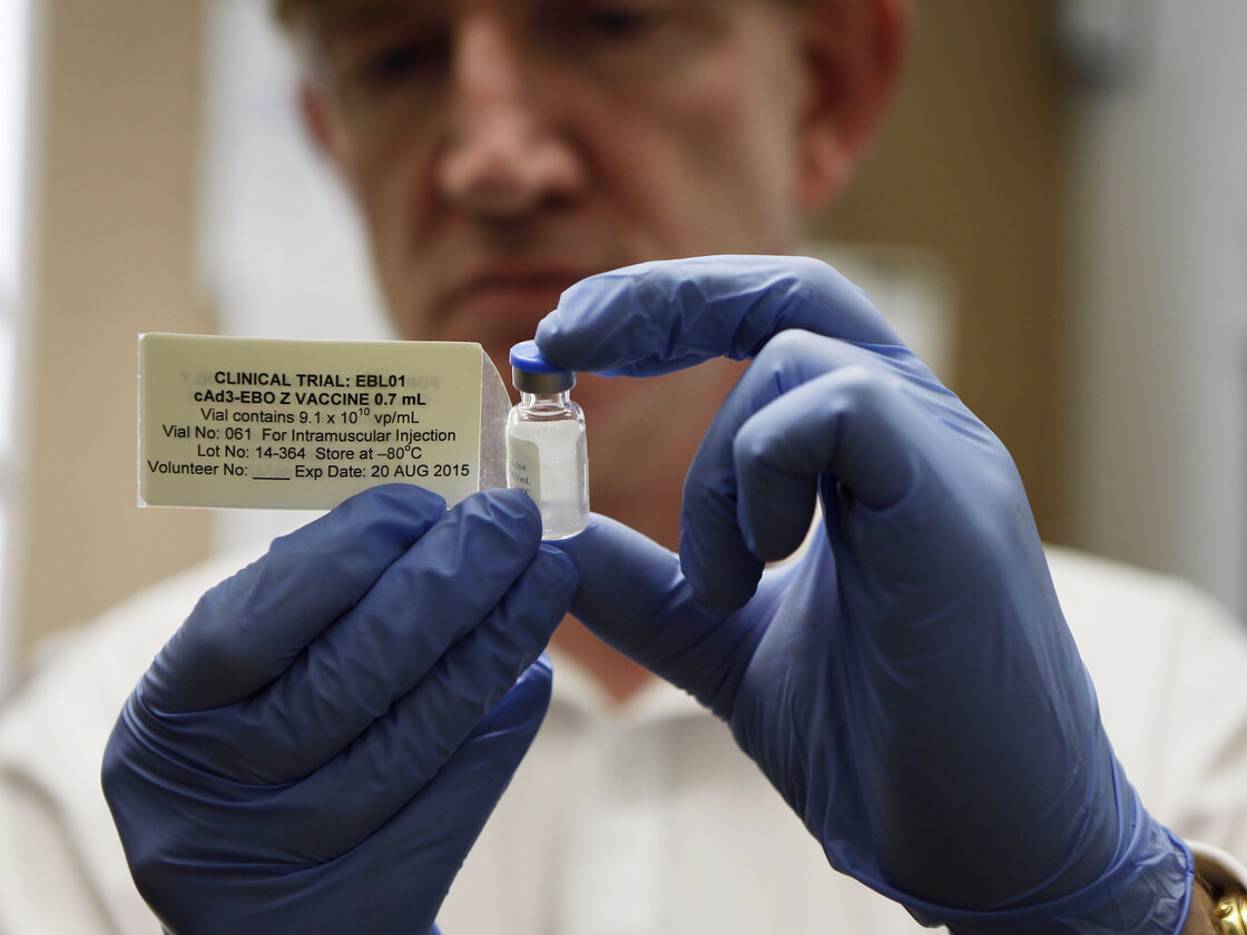 Adrian Hill, director of the Jenner Institute and chief investigator of the trials with an Ebola vaccine his organization developed, holds a vial of the vaccine.