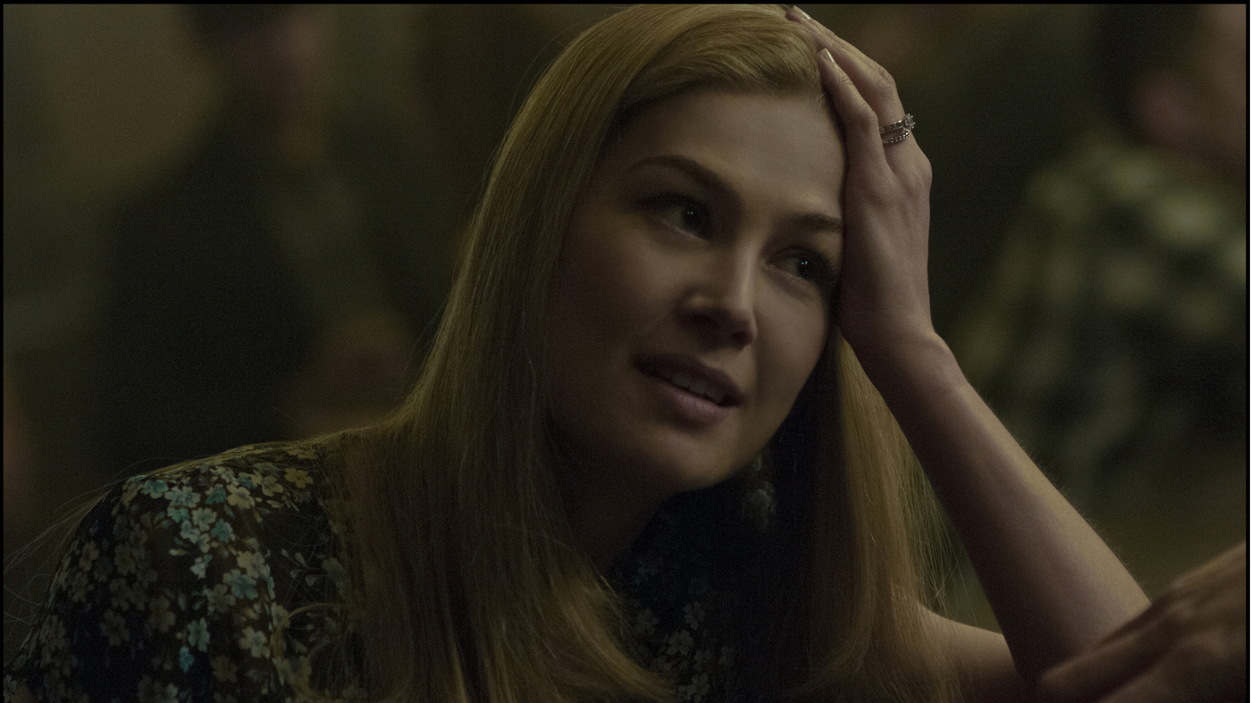Amy Dunne (Rosemund Pike) in conversation with someone in the film Gone Girl.