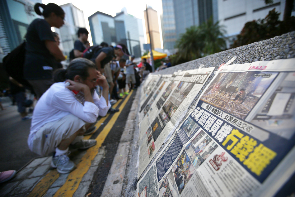 People read newspapers placed along a street blocked by protesters outside the government headquarters building in Hong Kong on Wednesday. While Hong Kong media are covering the protests closely, media in mainland China have been mostly quiet. (Carlos Barria/Reuters/Landov)
