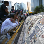 People read newspapers placed along a street blocked by protesters outside the government headquarters building in Hong Kong on Wednesday. While Hong Kong media are covering the protests closely, media in mainland China have been mostly quiet.