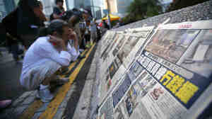 People read newspapers placed along a street blocked by protesters outside of the government headquarters building in Hong Kong on Wednesday. While Hong Kong media are covering the protests closely, media in mainland China have been mostly quiet.