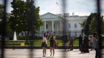 Visitors take photos in front of the White House.