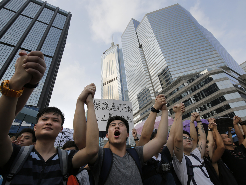 Protesters shout slogans outside a flag-raising ceremony that Hong Kong's embattled leader, Chief Executive Leung Chun-ying, attended in Hong Kong on Wednesday. (Vincent Yu/AP)