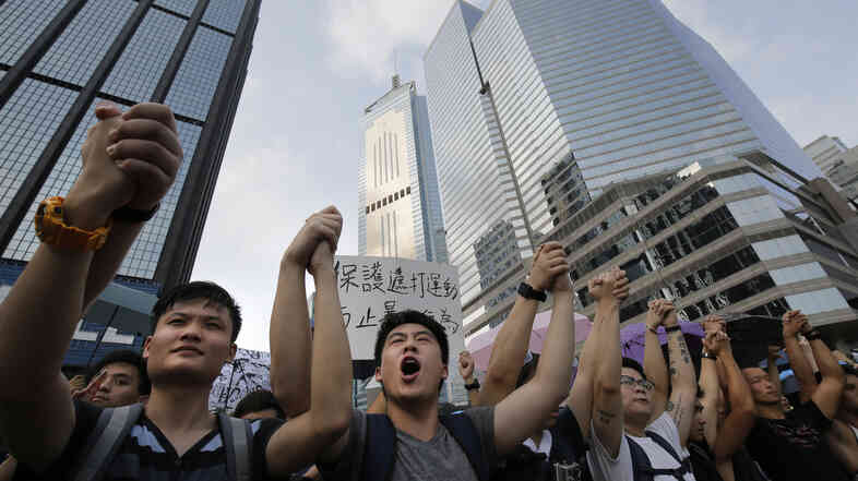 Protesters shout slogans outside a flag-raising ceremony that Hong Kong's embattled leader, Chief Executive Leung Chun-ying, attended in Hong Kong on Wednesday.