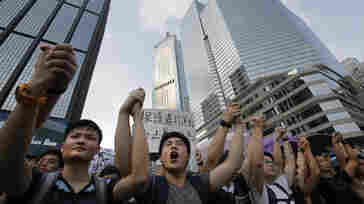 Protesters shout slogans outside a flag-raising ceremony where Hong Kong's embattled leader, Chief Executive Leung Chun-ying, attended in Hong Kong on Wednesday.
