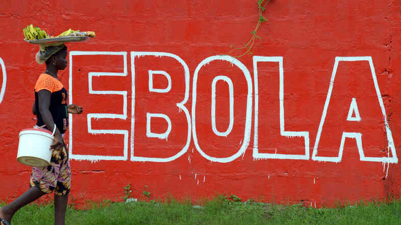 There's no escaping Ebola in West Africa. Here, a seller of bananas walks past a slogan painted on a wall in Monrovia, the capital of Liberia.
