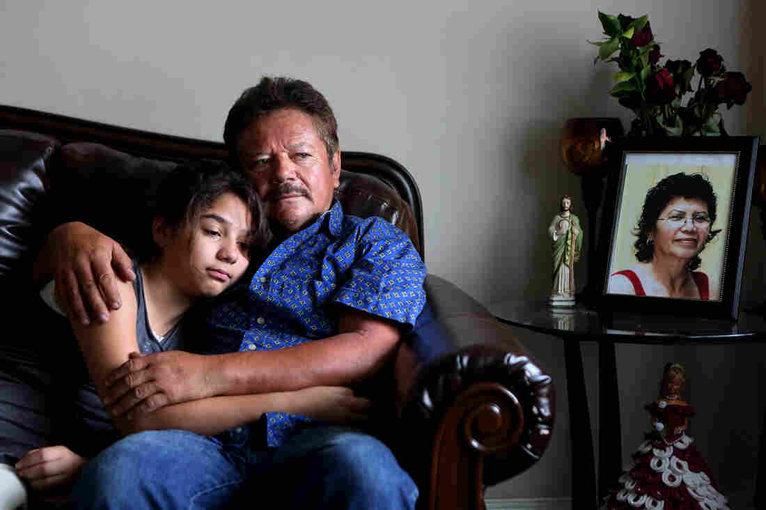 Guillermo Gomez, husband of Vilma Marenco, holds his daughter in their home in Northeast Houston. Marenco was killed in April after being hit by an uninsured trucker who ran a red light.