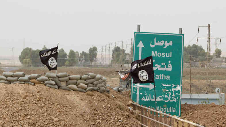 Islamic State flags on the Mullah Abdullah bridge in southern Kirkuk earlier this week. A U.N. report says the extremist group has perpetrated possible war crimes and crimes against humanity.