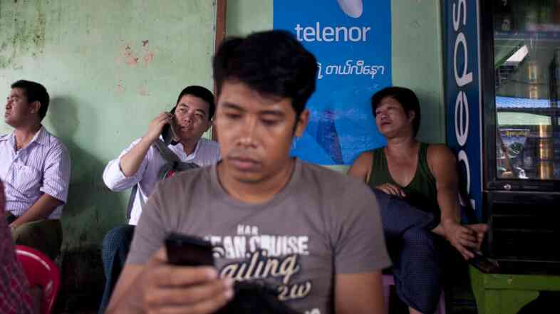 A man uses a mobile phone in front of a Telenor ad for cheap sim cards in Yangon, Myanmar. Cheap mobile technology has ignited an Internet revolution in the once-isolated nation.