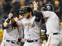 San Francisco Giants' Brandon Crawford, center, is greeted by teammates Brandon Belt, left, and Hunter Pence right, after hitting a grand slam against the Pittsburgh Pirates.