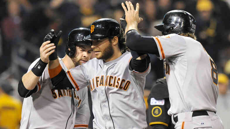 San Francisco Giants' Brandon Crawford, center, is greeted by teammates Brandon Belt, left, and Hunter Pence after hitting a grand slam against the Pittsburgh Pirates in the fourth inning of Wednesday night's game.