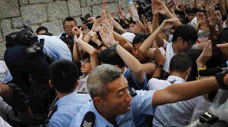Student protesters in Hong Kong resist during a change of shift for local police but backed down after being reassured they could reoccupy the pavement outside the government compound's gate.