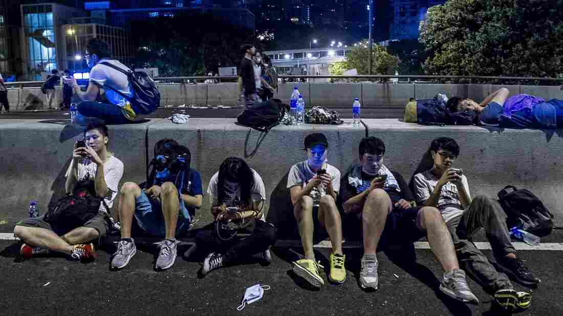 Protesters rest following pro-democracy protests in Hong Kong on Sept. 29. They're using old and new forms of tech to stay connected.