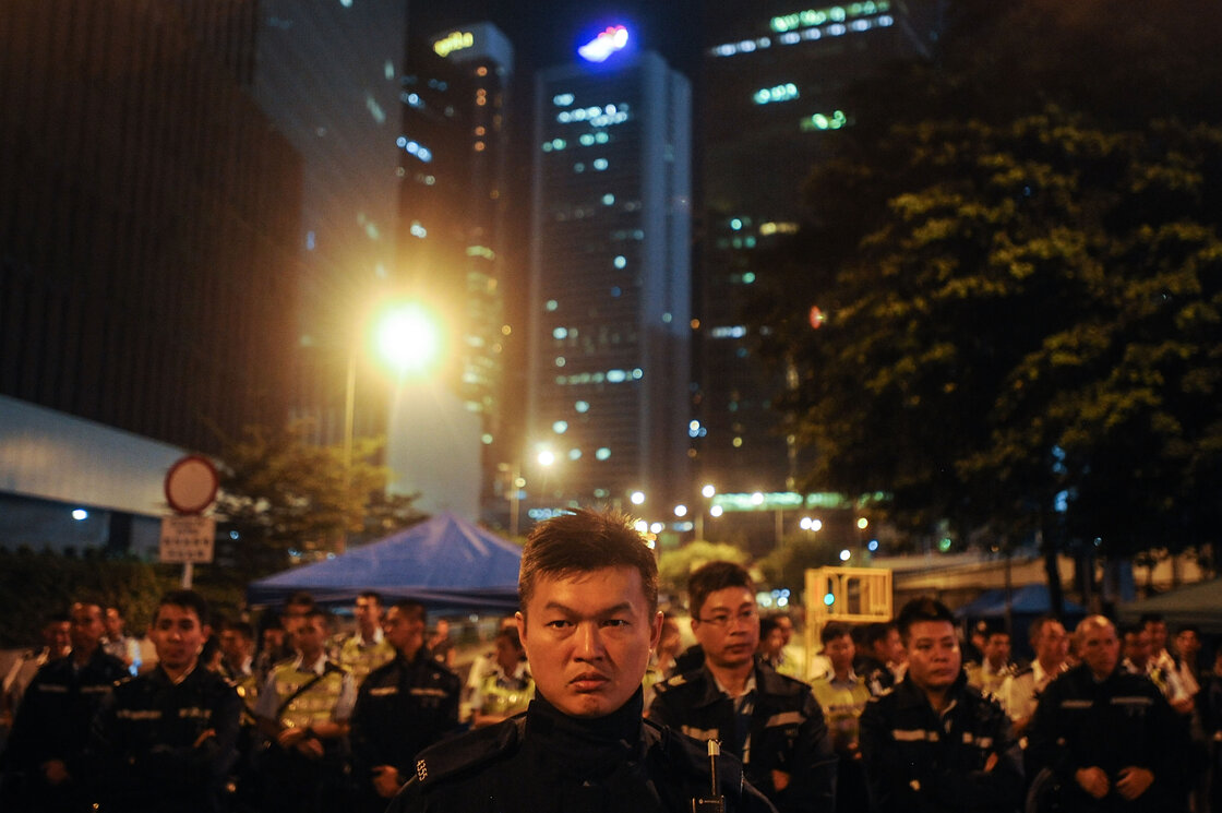 Police stand guard outside the government headquarters Friday in Hong Kong.