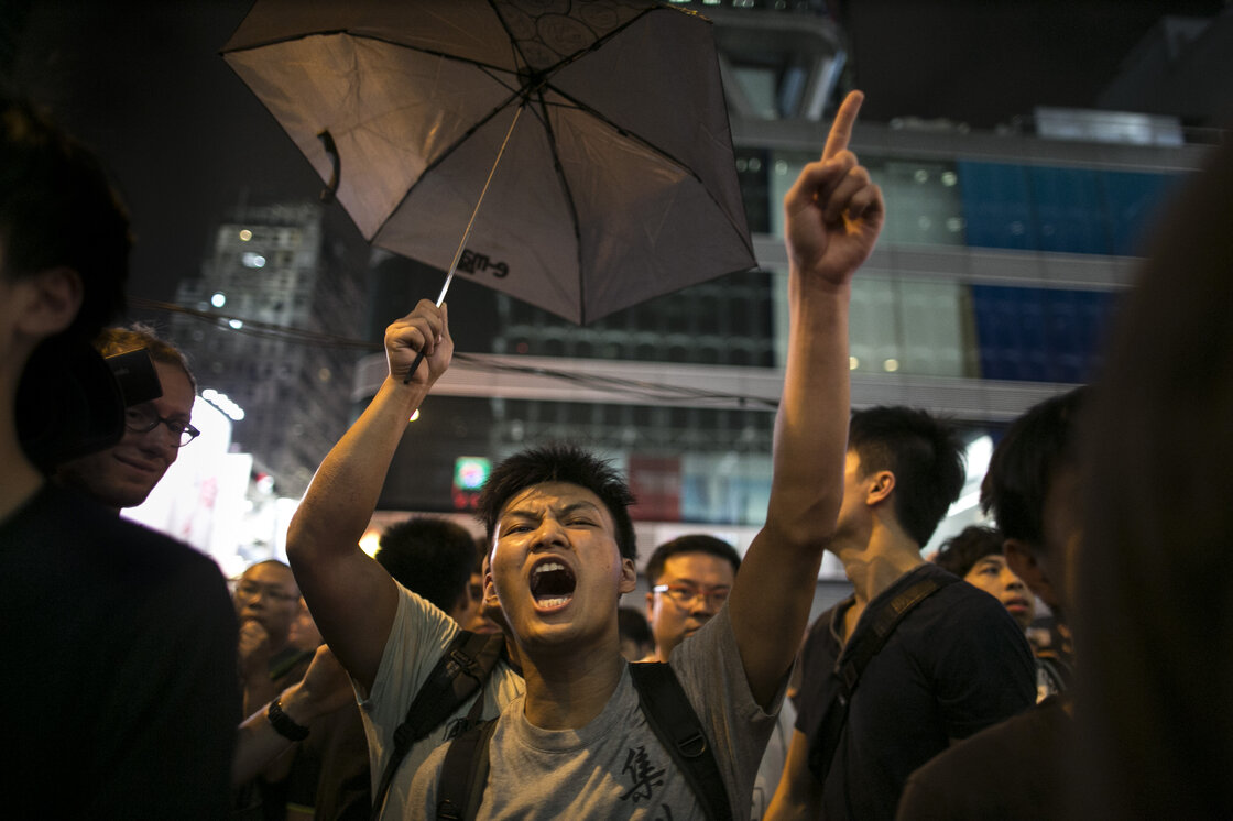 "Police are trying to control the crowds in the Mong Kok neighborhood as residents of Kowloon who are pro-Beijing clash with pro-democracy protesters, screaming at them to ""get out."""