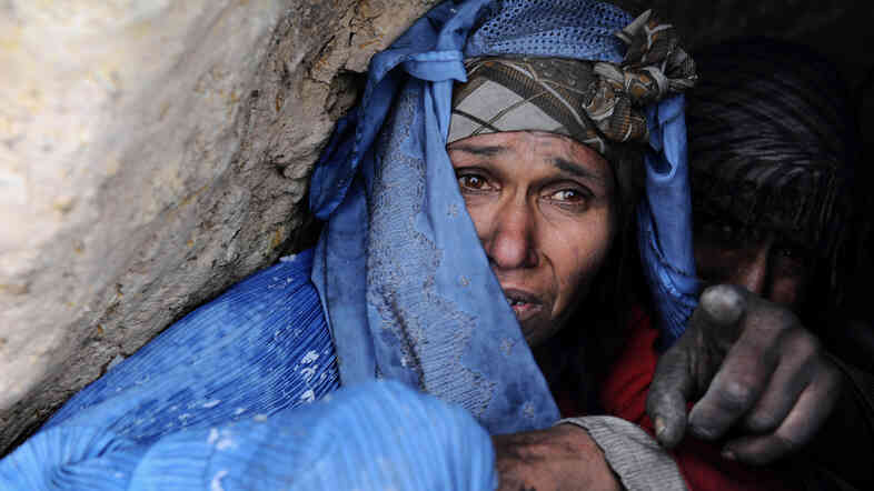 An Afghan woman addicted to drugs looks out from her hut on the outskirts of Herat, in western Afghanistan.