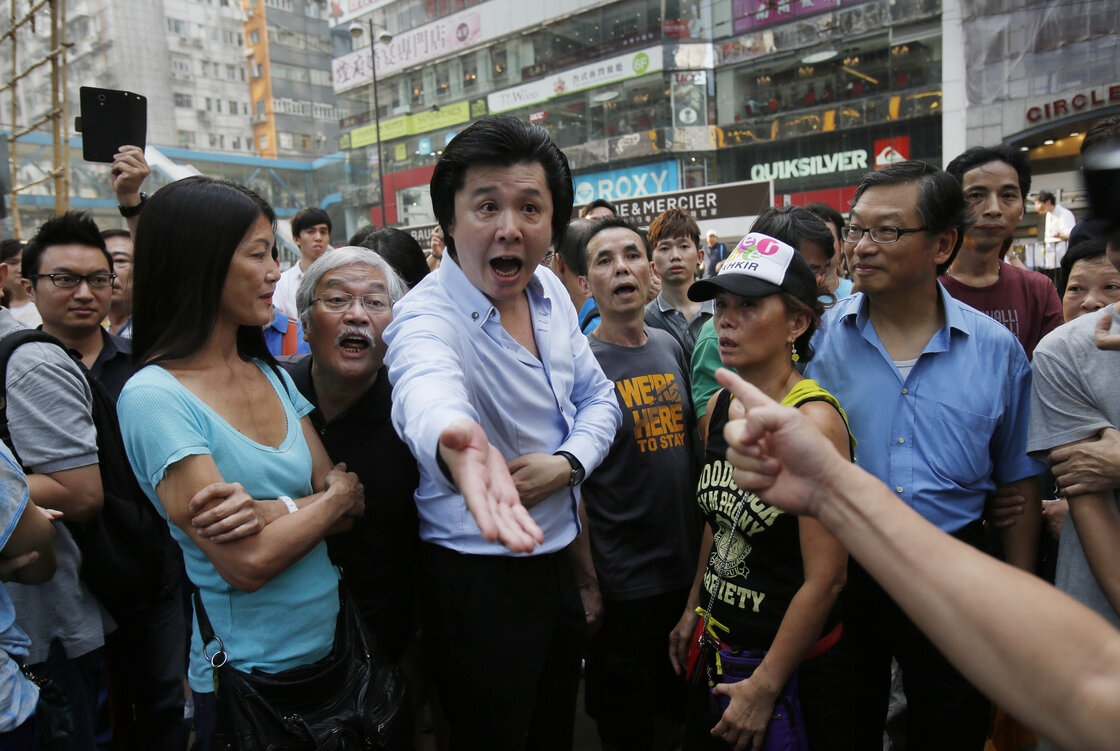Angry locals confront pro-democracy student protesters, demanding that they remove the barricades blocking local streets in Causeway Bay.