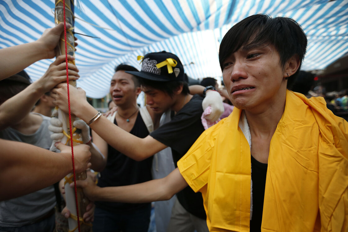 Student protesters are overwhelmed with emotions as they hold onto their tent while being threatened by residents and pro-Beijing supporters in Kowloon's crowded Mong Kok district.
