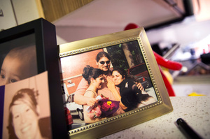 A photograph of Carlos Romero with his sisters in high school sits on the counter in Romero's apartment in Seattle.