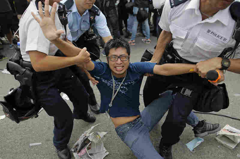 Police officers remove a pro-democracy protester at the compound of the chief executive office in Hong Kong on Friday. Hong Kong's main democracy groups called off planned talks with the territory's government after several hundred pro-Beijing demonstrators attacked activists who have staged a week of protests calling for greater freedom.
