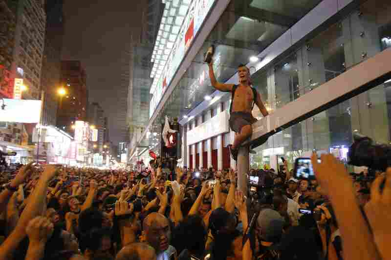 A pro-democracy student protester scales a traffic light pole in Mong Kok as local residents yell at him to leave the occupied area.