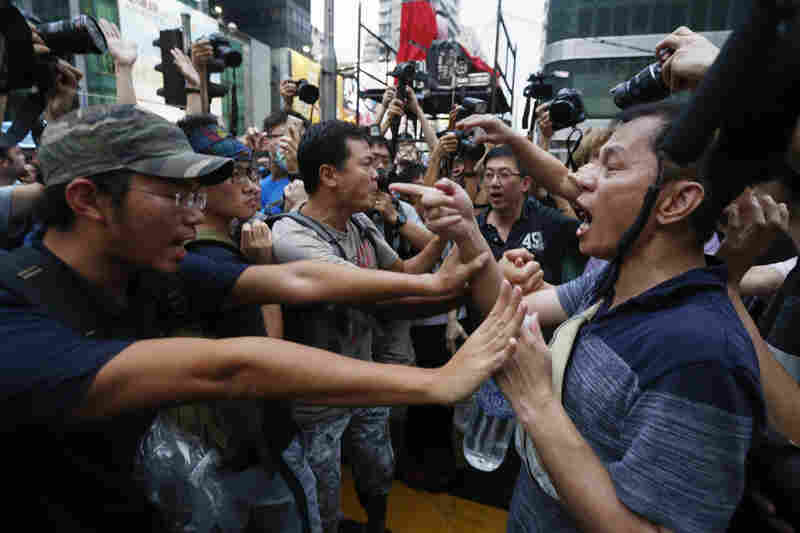 Pro-democracy protesters (left) stop an anti-Occupy Central protester from going near their tent in Mong Kok. Occupy Central protesters were angered that police did not stop the attack on their camp on Friday.