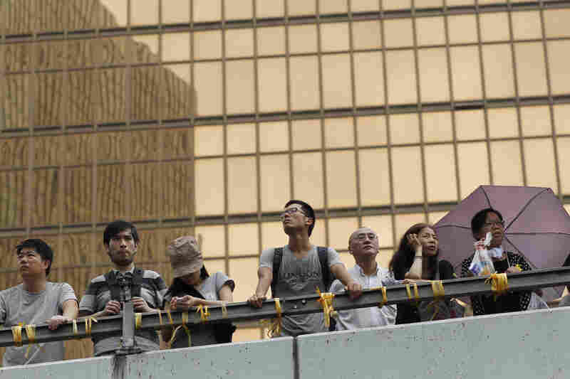 Onlookers watch the encampments of pro-democracy protesters outside the government complex.
