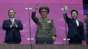 North Korea's National Defense Commission Vice Chairman Hwang Pyong So, middle, waves as the country's athletes march at the end of the Asian Games. He's flanked by Workers Party Secretary Choe Ryong Hae, right, and South Korea's Kim Kwan-jin, left, national security adviser to South Korea's president.