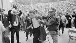 Mario Savio, leader of the Berkeley Free Speech Movement, is restrained by police as he walks to the platform at the University of California's Greek Theater in
