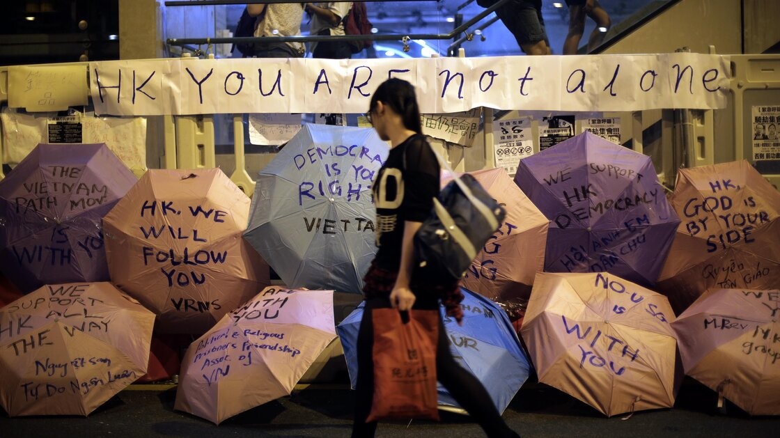 A woman walks past umbrellas with pro-democracy slogans written on them at a protest site near Hong Kong government headquarters on Saturday.