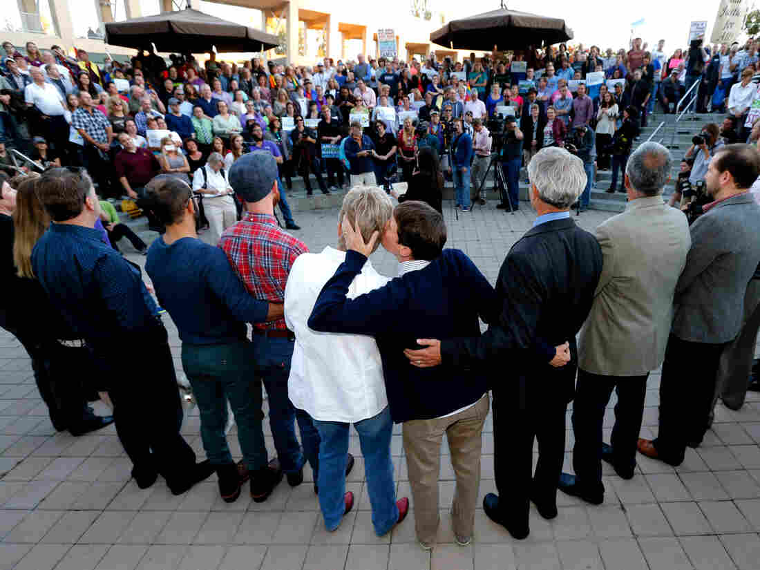 Kody Partridge (center right) and her partner, Lauri Wood, kiss at a same-sex marriage celebration Monday in Salt Lake City. The status of gay marriage remains uncertain in Kansas and Wyoming, where officials say no court has ruled on their ban specifically.