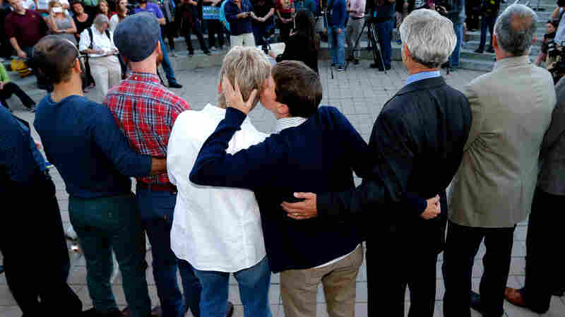 Kody Partridge (center right) and her partner, Lauri Wood, kiss at a same-sex marriage celebration Monday in Salt Lake City. The status of gay marriage remains uncertain in Kansas and Wyoming, where officials say no court has ruled on