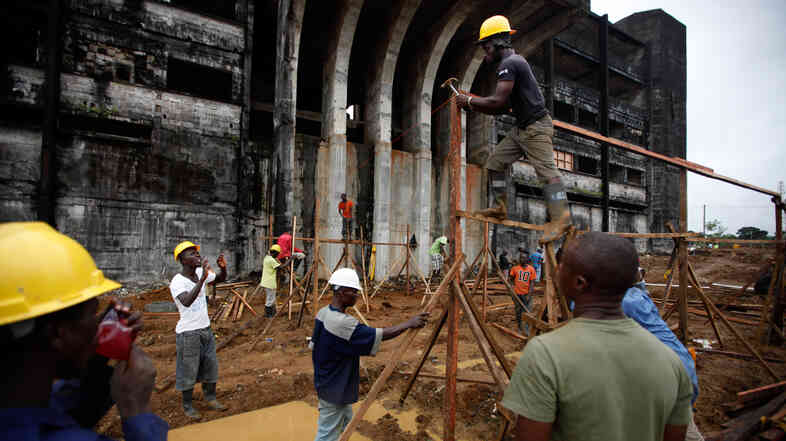 Workers construct framing at the back of the Ebola treatment unit in front of the former Ministry of Defense building in Monrovia, Liberia.