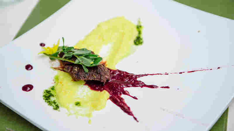 Another of Sherman's dishes — bison hanger steak with a corn and dandelion puree, chokecherries, purslane and squash blossoms.