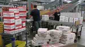 Employees pack copies of the new book Harry Potter and the Deathly Hallows for shipment in July 2007 at an Amazon fulfillment center in Fernley, Nev. Workers at the center filed a suit in 2013, seeking compensation for time spent in a mandatory security line after their shifts.