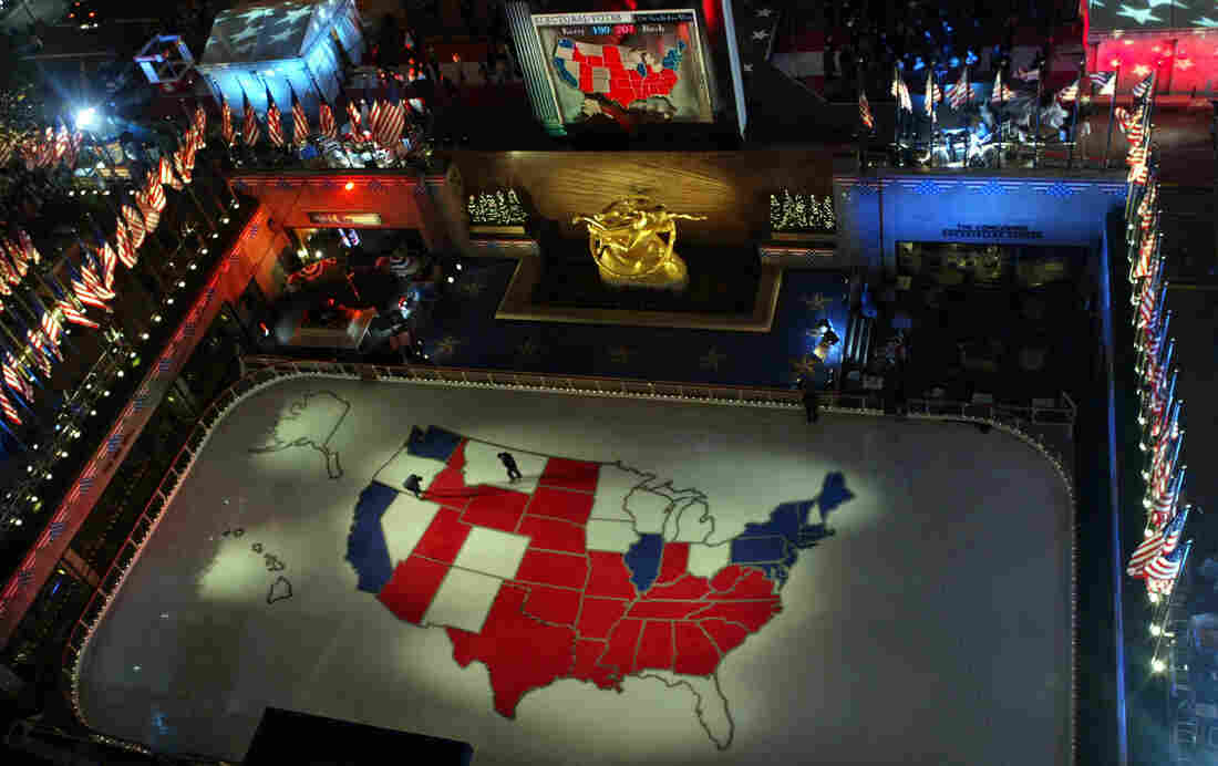 """Workers walk on a giant presidential election map of the U.S. made of ice in the skating rink at Rockefeller Center in 2004. The media still use """"red"""" and """"blue when talking about the electoral map, but not for a deep cultural divide."""