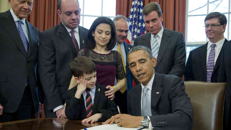 President Obama, is watched by Mark Miller, back second from left, Ellyn Miller, and their son Jake Miller, left, as he signs the Gabriella Miller Kids First Research Act, into law in the Oval Office this spring. The Democratic and Republican parties complained to the Federal Election Commission that the law took away public funding for their political conventions.