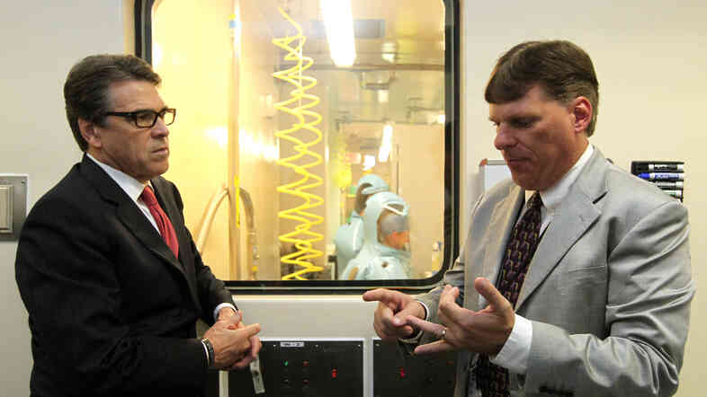 Texas Gov. Rick Perry (left) listens to Tom Geisbert, a professor of microbiology and immunology at the University of Texas Medical Branch, explain the work researchers are conducting in a lab in the Galveston National Laboratory on Tuesday. Numerous Republicans, including Perry, have linked the first Ebola case diagnosed in the U.S. to border control and other political issues.
