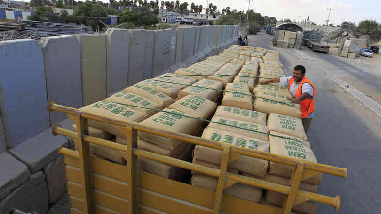 A Palestinian worker checks a truck loaded with bags of cement as it crosses into southern Gaza from Israel last year. Israel has restricted cement supplies to only specific projects.