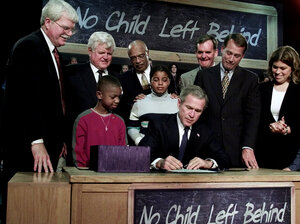 President George W. Bush, seated, signs No Child Left Behind into law at Hamilton High School in Hamilton, Ohio.