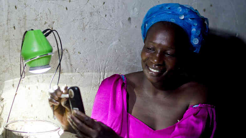 A woman in Senegal charges her cellphone using a port in her solar-powered LED lantern.