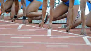 Female sprinters in the starting blocks.