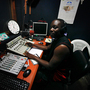 Elliott Adekoya, 31, aka The Milkman, is a DJ at Monrovia's Sky FM radio, pictured here his DJ booth. He is also part of a group of 45 Liberian musicians called the Save Liberia Project. They want to get the word out that Ebola is real, but it is not a death sentence. He says that message, which was propagated early on by the Ministry of Health, actually contributed to the problem.