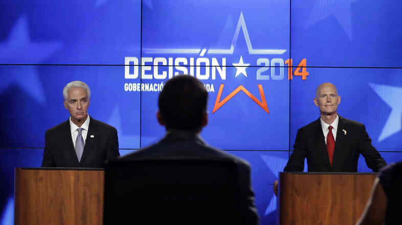 Democrat Charlie Crist, a former Republican governor of Florida (left), and Rick Scott, the current Republican governor of Florida, listen to the moderators during a gubernatorial debate on Friday. The two are facing off in a tight race that's fueling a barrage of negative campaign ads.