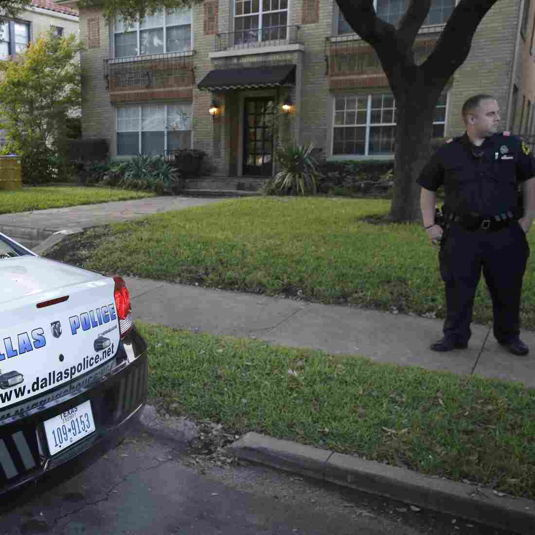 Police stand guard outside the apartment of a hospital worker who has tested positive for Ebola in Dallas Sunday. In the background is a yellow barrel used to dispose of hazardous materials.