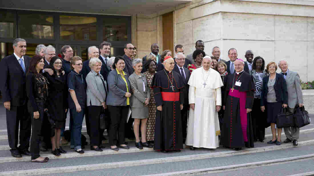 Pope Francis poses for a photo with lay members as he arrives for an afternoon session of a two-week synod on family issues on Friday. On Monday, the Vatican issued a midway report from the Vatican expressing increased tolerance for gays and unmarried couples.