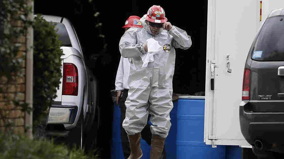 A Protect Environmental worker wears a hazard suit Oct. 13 in a staging area at the apartment of a Dallas nurse who tested positive for Ebola.
