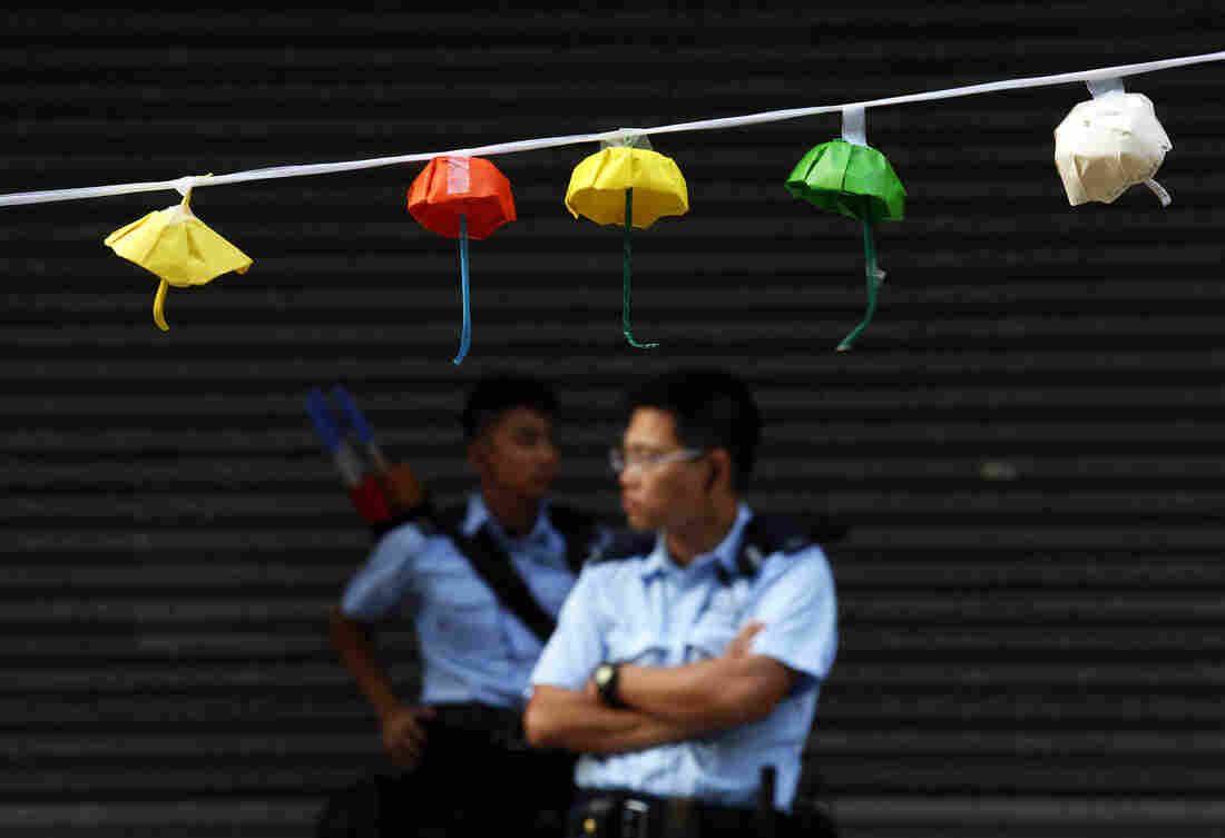 Policemen stand guard on a blocked road behind an installation of paper umbrellas, considered a symbol of the Occupy Central movement, at the Causeway Bay shopping district in Hong Kong on Tuesday.
