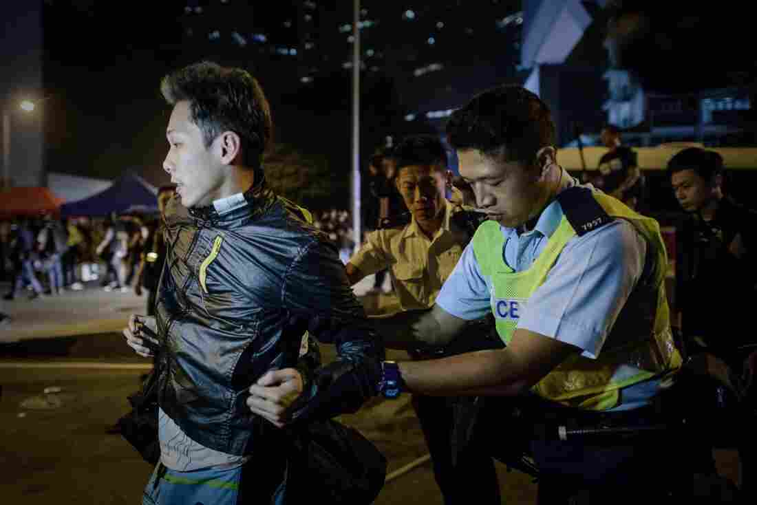 Police forces arrest a pro-democracy protester outside the central government offices in Hong Kong.