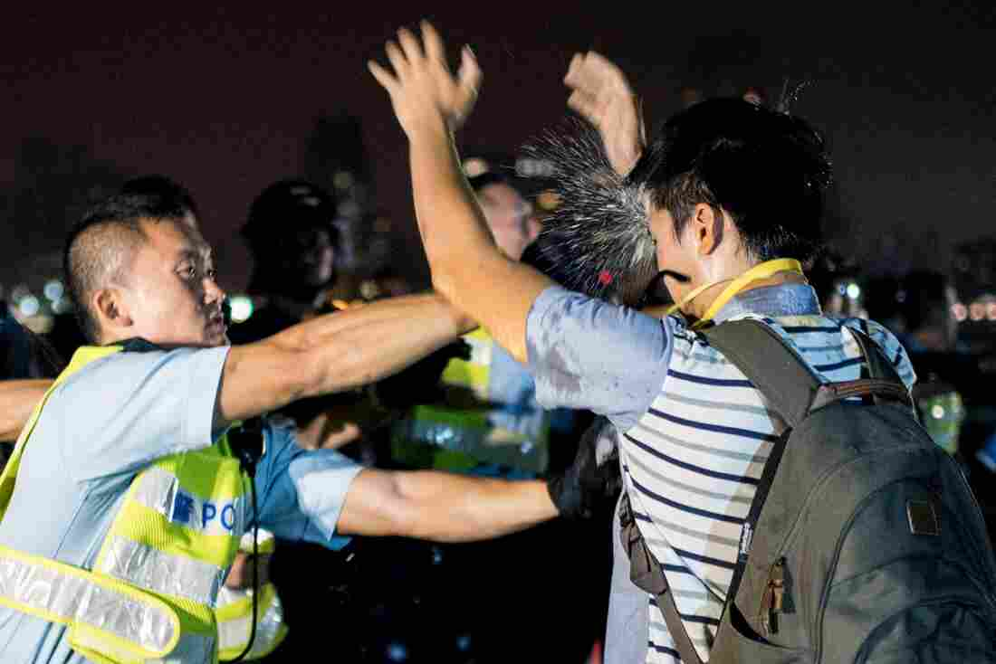 A police officer sprays a pro-democracy protester in the face with pepper spray in Hong Kong on Wednesday.
